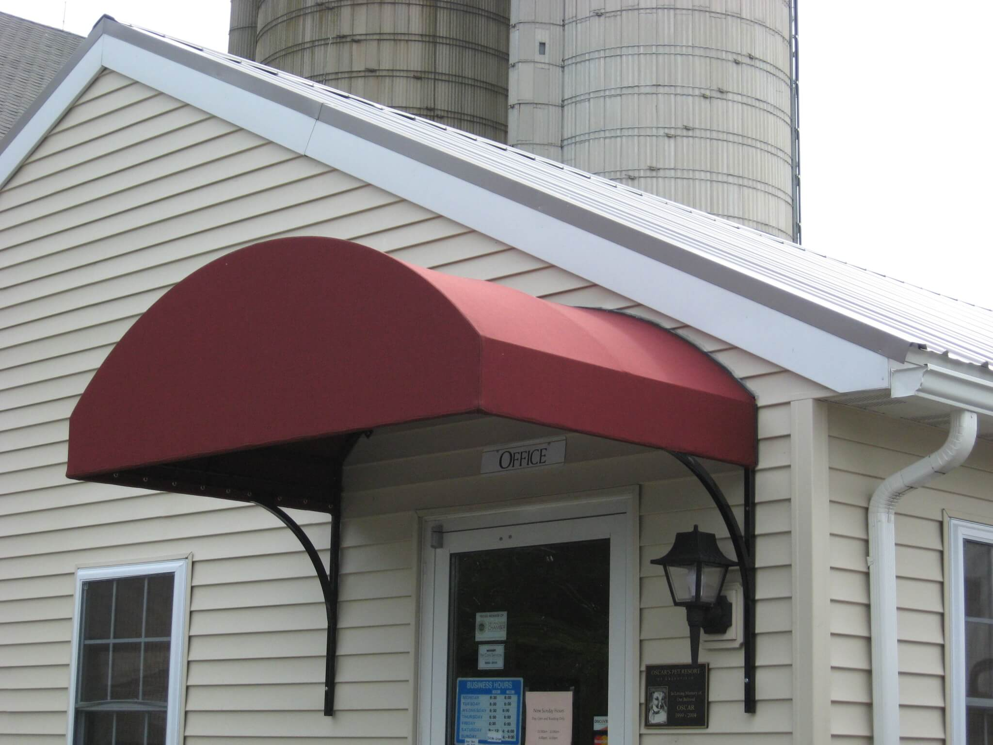Arched canvas commercial awning installed over a door ...