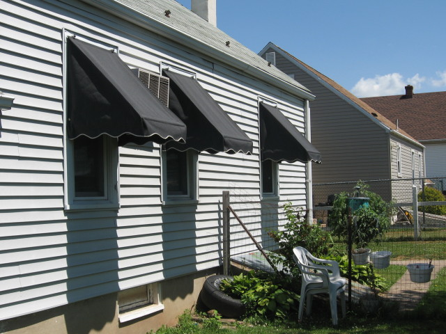 Traditional style window awnings. gray Sunbrella fabric