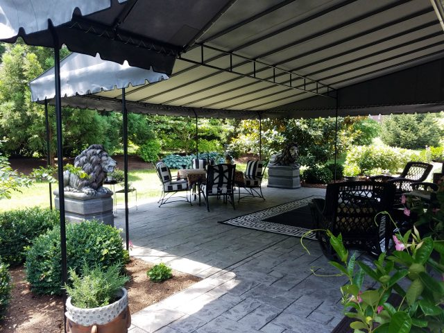 Grey Sunbrella fabric fixed awning over a patio