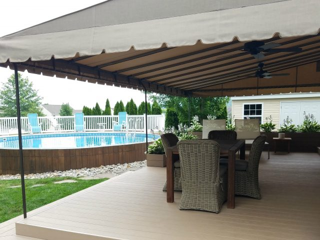 Beige Sunbrella deck awning with ceiling fans