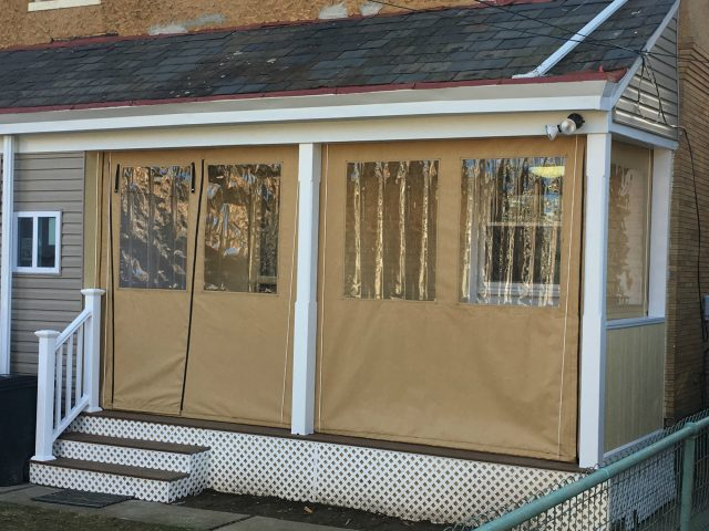 Porch enclosure drop curtains with clear vinyl windows and a zippered door